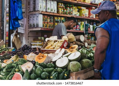 London, UK - July 16, 2019: Man buys fresh fruits and vegetables from a market stall at Brixton Market, a community market run by local traders in the centre of Brixton, south London.