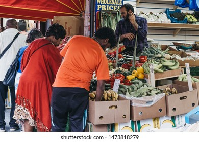 London, UK - July 16, 2019: People buy fresh fruits and vegetables from a market stall at Brixton Market, a community market run by local traders in the centre of Brixton, south London.