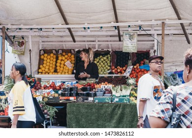 London, UK - July 16, 2019: Fresh fruits and vegetables on sale in Brixton Market, a community market run by local traders in the centre of Brixton, South London. Selective focus, motion blur.