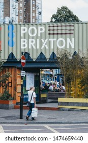 London, UK - July 16, 2019: Man walking in front of Pop Brixton, event venue and the home of a community of independent retailers, restaurants, street food startups and social enterprises.
