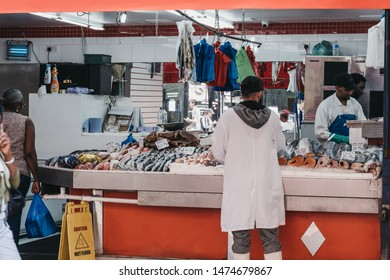 London, UK - July 16, 2019: View from outside of people working inside fishmongers shop at Brixton Market, a community market run by local traders in the centre of Brixton, south London.