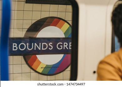 London, UK - July 16, 2019: View of Bounds Green station Rainbow Pride roundels through the window of tube carriage. London Underground roundels were change to celebrate Pride in London