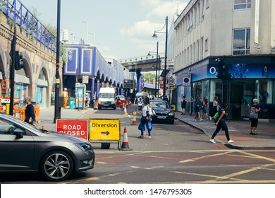 London / UK - July 16, 2019: people crossing Atlantic Road towards Coldharbour Lane; Brixton railroad station on the left