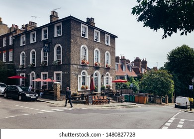 London, UK - July 17, 2019: Man walking past the Wells Tavern a public house at 30 Well Walk, Hampstead, London. It was built in about 1849