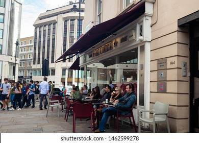 London / UK - July 18, 2019: people seating outside Pret a Manger drinking coffee and relaxing. Pret is a popular international sandwich shop chain, based in UK