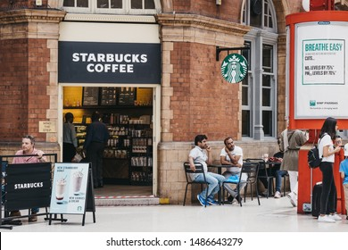 London, UK - July 18, 2019: People at the tables of Starbucks inside Marylebone Station, London. Starbucks is a famous American coffeehouse chain.