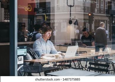 London, UK - July 18, 2019: Through the window of men working on laptops inside a cafe in Marylebone, a chic residential area of London famous for baker Street and Madame Tussauds waxwork museum.