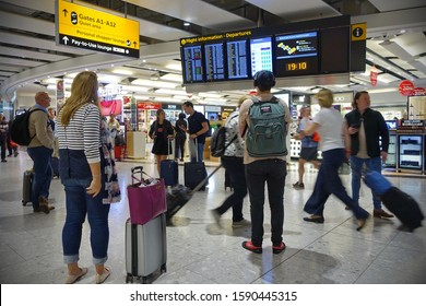 London, UK - July 18, 2019: Air travelers check a departures board at a busy Heahthrow Airport terminal. Heathrow is one of the busiest airports in the world and busiest in Europe by passenger volume.
