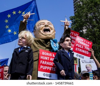 London, UK - July 20, 2019. Anti Brexit protest. Stilts walker impersonating  Nigel Farage holding puppets of Boris Johnson of Jeremy Hunt. Stunt by Best for Britain campaign.