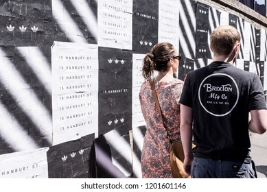 London, UK - July 2018: Couple photographed from behind walking on a street in Brixton next to a wall covered in black and white posters. Brixton, Lambeth, South London, UK