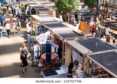 London, UK - July 2018: People shopping and walking around the stalls in Old Spitalfields indoor market. Spitalfields, East London, UK