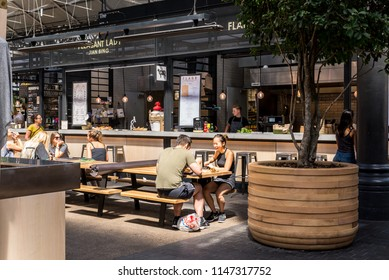 London, UK - July 2018: People eating at the  Old Spitalfields indoor market. Spitalfields, East London, UK
