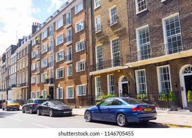 London, UK - July 2018. London street with cars parked on the road and Georgian restored residential townhouses in yellow bricks