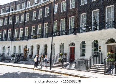 London, UK - July 2018: Three girls walking in front of the Crescent Hotel, Cartright Gardens, Bloomsbury, London, UK