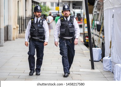 London, UK, July, 2019. Two British Police officers patrolling the streets of England wearing stab vests. Oxford Street