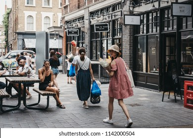 London, UK - July 22, 2018: People walking in Spitalfields Market, one of the finest surviving Victorian Market Halls in London with stalls offering fashion, antiques and food.