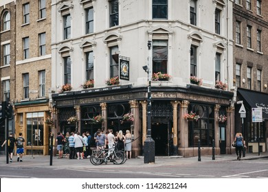 London, UK - July 22, 2018: People standing and drinking outside The Ten Bells pub in Shoreditch, East London, pub famous for its supposed association with two victims of Jack the Ripper.