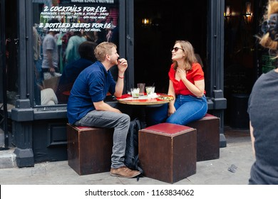 London, UK - July 22, 2018: Young couple talking in a street cafe on the Brick Lane in London, UK