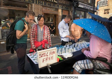 London, UK - July 22, 2018: Man playing chess with passers by in Brick Lane, London. The street is the heart of the London's Bangladeshi-Sylheti community and is famous for its many curry houses.