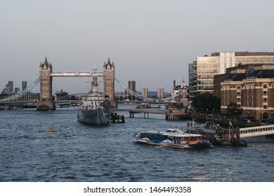 London, UK - July 23, 2019: View of Thames Clipper boat at London Bridge City Pier, HM Belfast and Tower Bridge on the background, selective focus. Tower Bridge is an iconic symbol of London.