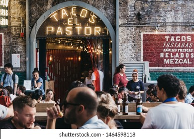 London, UK - July 23, 2019: People sitting at the outdoor tables of El Pastor Tacos restaurant in Borough Market, one of the largest and oldest food markets in London. Selective focus.
