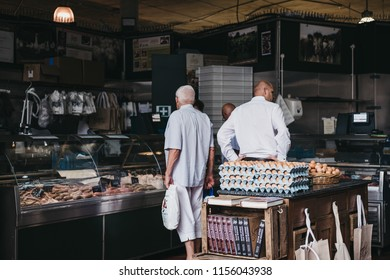 London, UK - July 24, 2018: Customers inside a butcher's stand at Borough Market, one of the largest and oldest food markets in London.