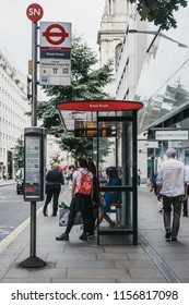 London, UK - July 24, 2018: People waiting for a bus on the Bread Street bus stop in the City of London, London's famous financial district.