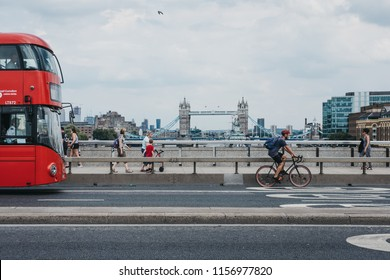 London, UK - July 24, 2018: Cyclist, pedestrians and double decker bus on London Bridge, London, UK, River Thames and Tower Bridge on the background. Cycling is a popular way to get around the city.