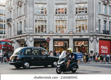London, UK - July 24, 2018: Taxi and people in front of flagship H&M store on Oxford Street near entrance to Oxford Circus tube station, the busiest rapid-transit station in the United Kingdom.