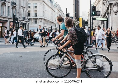 London, UK - July 24, 2018: Cyclists waiting for traffic lights on Oxford Street near entrance to Oxford Circus tube station, the busiest rapid-transit station in the United Kingdom.