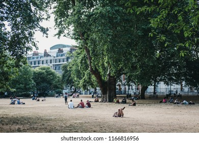 London, UK - July 24, 2018: People relaxing in Lincoln's Inn Fields during summer 2018 heatwave in London, UK. Lincoln's Inn Fields is the largest public square in London.