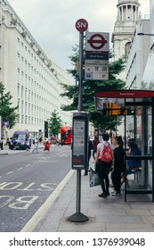 London / UK - July 24, 2018: people waiting for a bus on Bread Street bus stop on Cheapside Street in the City Of London on a warm sunny day
