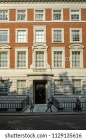LONDON, UK - JULY 25, 2017:  Office workers walking home past the imposing office and apartment block in Grosvenor Square, London that was once home to the US Ambassador Walter Hines Page during WWI.