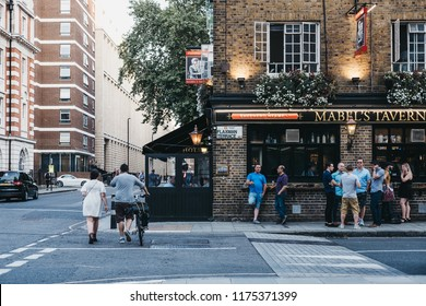 London, UK - July 26, 2018: People and cars in front of Mabel's Tavern pub, a popular Shepherd Neame pub close to Euston and King's Cross, London, UK.