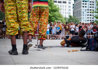 London / UK - July 26th 2018: A group of performers dressed in colourful clothes limbo dance on the street to crowds of tourists