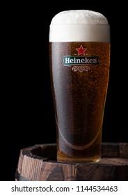 LONDON, UK - JULY 28, 2018: Original glass of Heineken Lager Beer on wooden barrel on black  background. Heineken is the flagship product of Heineken International