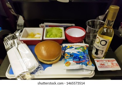 London, UK - July 29, 2019: In-flight dinner burger menu served in a Japan Airlines flight departing from Tokyo. This menu is a special serving prepared by Mos burgers, the famous japanese company.