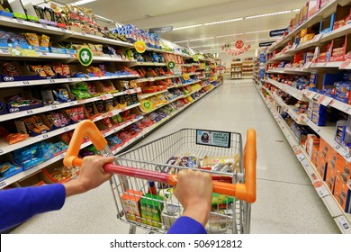 London, UK - July 3, 2014: A shopper pushes a trolley while browsing an aisle at a Sainsbury's supermarket. Sainsbury's is the UK's 2nd largest supermarket with a revenue of GBP23 billion in 2013.