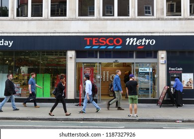 LONDON, UK - JULY 6, 2016: People walk by Tesco Express grocery store in London. Tesco had 5,500 stores as of 2017.