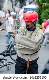 London / UK - July 6 2019: Street artist in a strait jacket shows Houdini style magic tricks, where he performs escape act. Taken in one of the London streets during the Gay Pride celebration.