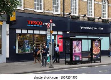 LONDON, UK - JULY 7, 2016: People walk by Tesco Express grocery store in London. Tesco had 5,500 stores as of 2017.