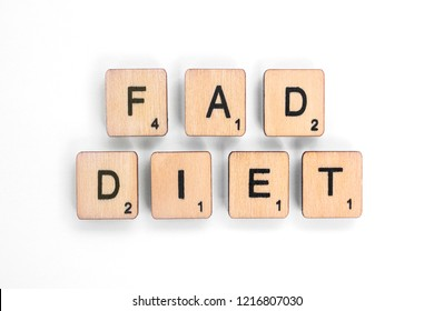 London, UK - July 8th 2018: The phrase FAD DIET - spelt with wooden letter tiles over a white background.