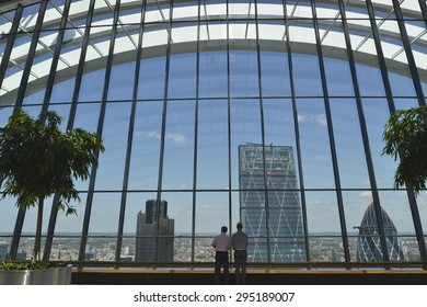 LONDON, UK - JULY 9, 2015: View from the SkyGarden at 20 Fenchurch Street.  2 men look out towards The Leadenhall Building, The Gherkin (30 St Mary Axe) and Tower 42 in London UK.
