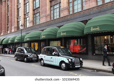 LONDON, UK - JULY 9, 2016: Black cabs wait at Harrods department store in London. The famous retail establishment is located on Brompton Road in Knightsbridge district.