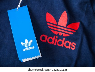 LONDON, UK - JUNE 05, 2019: Adidas Originals Label red color on blue fabric with shopping tag.