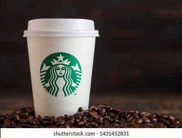 LONDON, UK - JUNE 05, 2019: Starbucks Coffee Paper Cup for take away with coffee beans on wooden background.