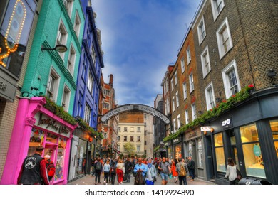 LONDON UK, JUNE 1, 2019:Colorful HDR image of tourists at the famous Carnaby Street in the center of London with its colorful houses, shops and restaurants on blue cloudy sky