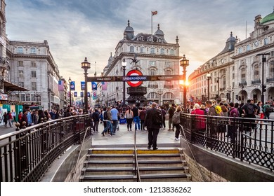 LONDON, UK - JUNE 10, 2018: The historic architecture of London in the UK at sunset at Piccadilly Circus with lots of locals and tourists passing by and enjoying themselves.