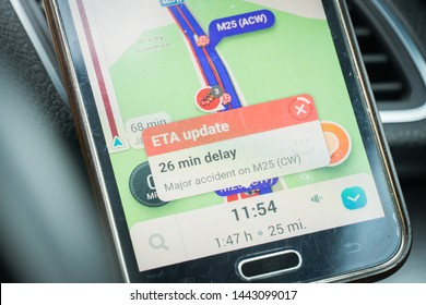 London, UK - June 11, 2019 - standstill traffic jam on m25 motorway; smartphone screen with GPS navigation showing delay
