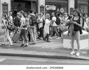 LONDON, UK - JUNE 12, 2015: Tourists in busy central London street in black and white